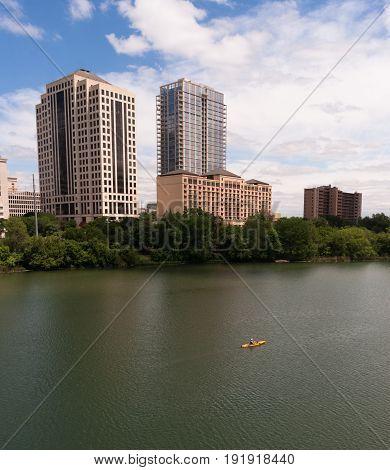 A Kayaker moves along the Colorado River dwarfed by the Austin Skyline