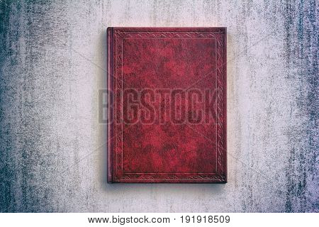 the book in a red cover over gray grunge background top view with vignette