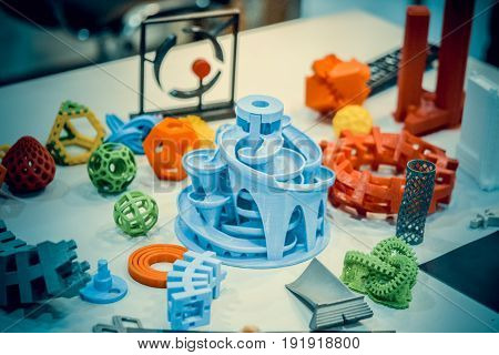 Models printed by 3d printer. Copy space. Bright colorful objects printed on a 3d printer on a table. Modern additive technologies 4.0 industrial revolution