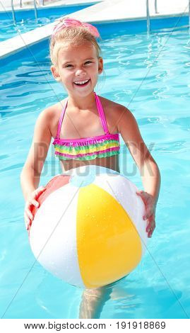 Cute smiling little girl with ball in swimming pool