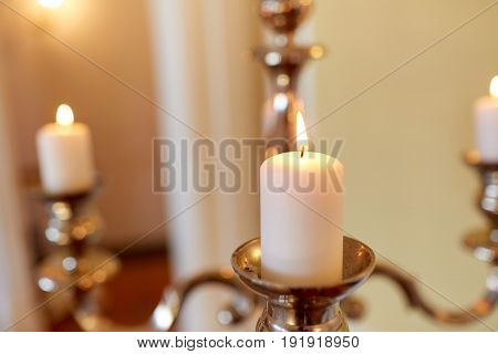 religion concept - candles burning in church