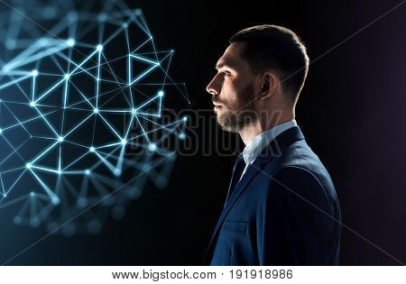 business, network, people and technology concept - businessman in suit looking at virtual low poly projection over black background