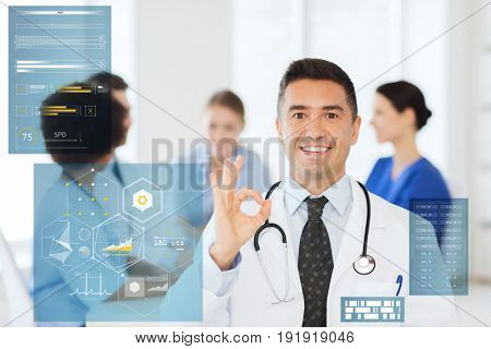 medicine, healthcare, technology and people concept - happy male doctor over group of medics meeting at hospital showing ok hand sign
