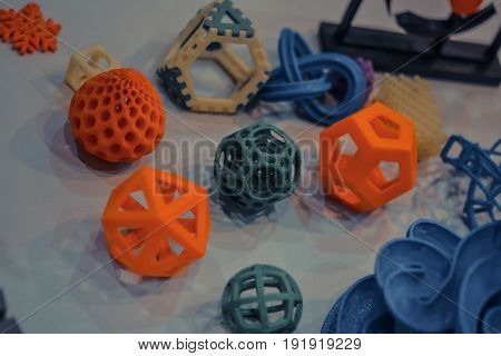Models printed by 3d printer. Dark. Bright colorful objects printed on a 3d printer on a table. Modern additive technologies 4.0 industrial revolution