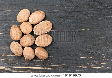 Few nutmegs on an empty wooden background, top view