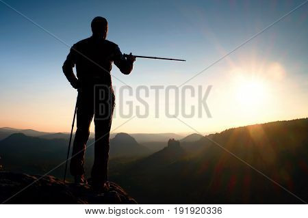 Tourist Guide Show The Right Way With Pole In Hand. Hiker With Sporty Backpack Stand On Rocky View P