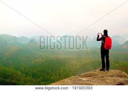 Tourist With Backpack Takes Photos With Smart Phone Of Rainy Vally. Dreamy Foggy Valley Below