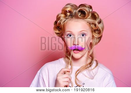 Portrait of a pretty girl teenager with curlers in her blonde hair making faces with mask. Teen style, fashionable teen girl. Cosmetics and make-up.