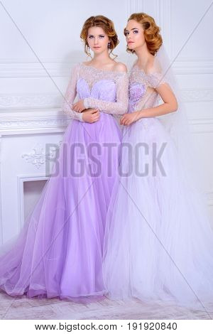 Charming bride and bridesmaid stand together in beautiful dresses and laugh. Wedding fashion.
