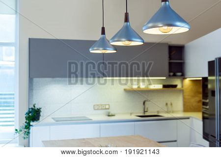 Modern home interior. Modern kitchen design in light interior. There is also a kitchen island in the room. Kitchen and living room combined. European furniture, design, technologies. Painted facades.