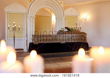 funeral and mourning concept - burning candles and coffin at orthodox church