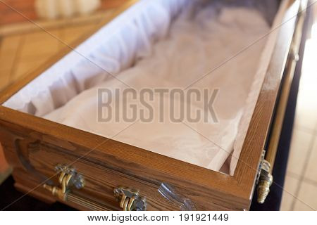 funeral and mourning concept - close up of open empty coffin in church