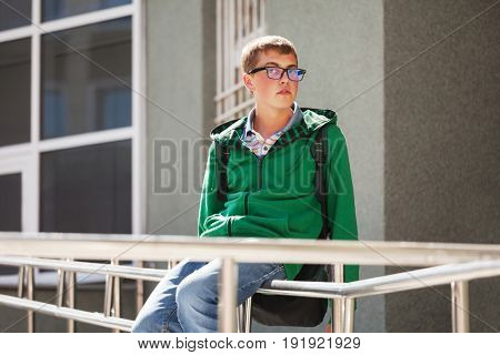 Teen boy in a hoodie against school building. Stylish male model in green hoodie and blue jeans
