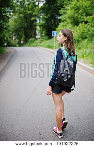 Sport Girl At Sportswear With Backpack Walking In A Green Park. A Healthy Lifestyle.
