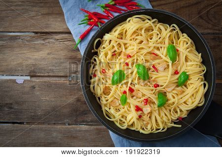 Noodles with garlic and chili on pan with basil decoration