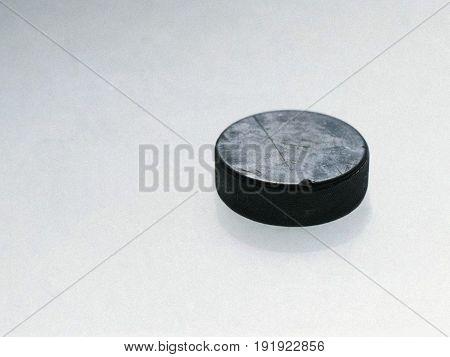 Ice hockey puck sliding on snowy ice