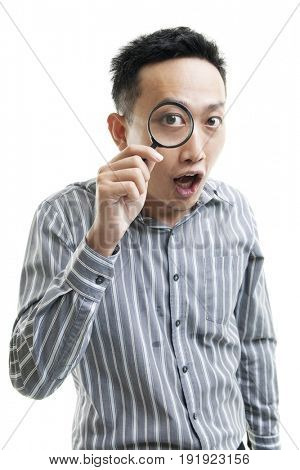 Asian business man discover concept by holding magnifier glass on one eye, standing isolated on white background