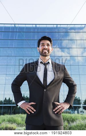 Arabic serious smiling happy successful businessman or worker in black suit with tie and shirt with beard and hands in the sides standing in front of an office building.