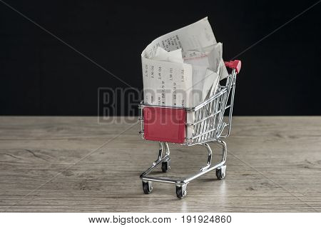 Close up shot of a tiny shopping trolley filled with receipts