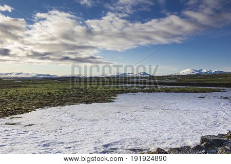 Wide icelandic landscape with snow and volcanoes