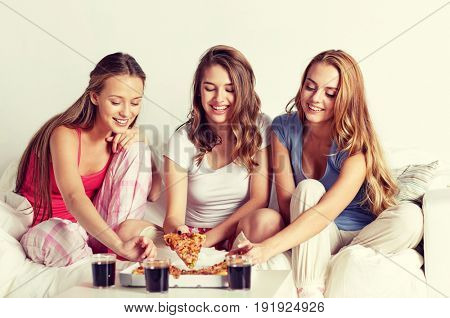 friendship, people, pajama party and junk food concept - happy friends or teenage girls eating pizza at home