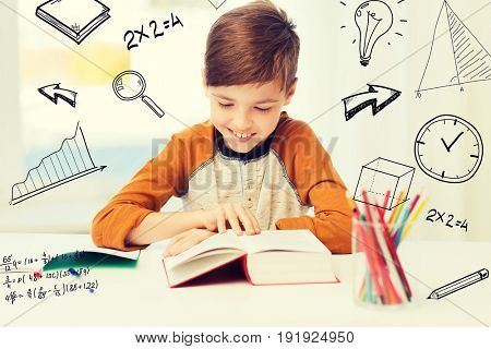 education, childhood, people, homework and school concept - happy student boy reading book or textbook at home over mathematical doodles