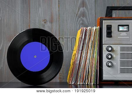 A pile of old vinyl records and audio equipment stand on a shelf against the background of a wooden wall