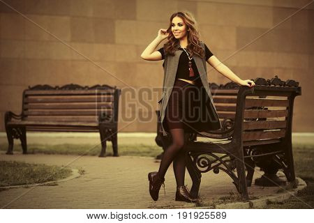 Happy young woman with long curly hairs walking in city street. Stylish fashion model in sleeveless coat outdoor