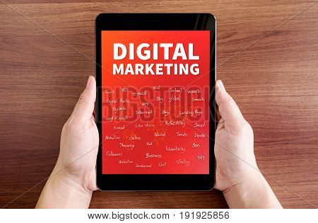 Two Hand Holding Tablet With Digital Marketing And Feature Word On Screen At Dark Brown Table Top,di