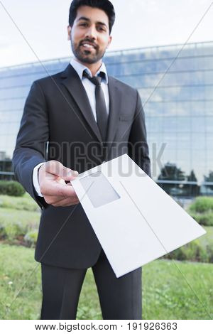 Arabic serious smiling happy successful businessman or worker in black suit with tie and shirt with beard gives a letter standing in front of an office building.