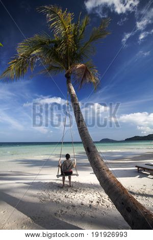 Young woman sitting on the swing near the palm trees on caribbean tropical beach