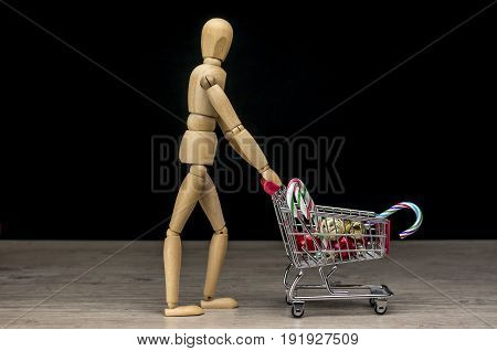 Wooden human mannequin holding shopping trolley filled with Christmas decorations