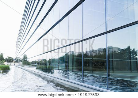 Big modern glass minimalistic office building or factory near lake in daylight.