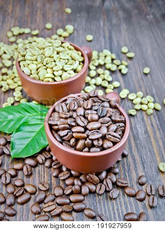 Grains of green and black coffee in brown clay cups and on a table with leaves on a background of a dark wooden board