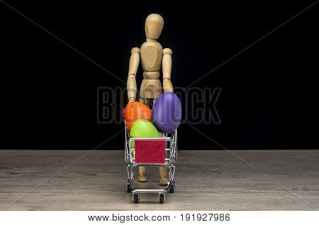 Wooden human mannequin holding shopping trolley filled with Easter eggs