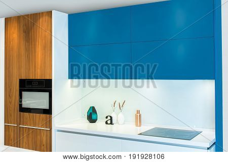 Modern home interior. Modern kitchen design in a light interior. Facades are painted and made of natural walnut veneer. European furniture, design, technologies.