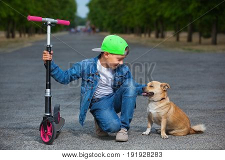 A small boy with a scooter sits next to a dog and strokes her in the park for a walk.