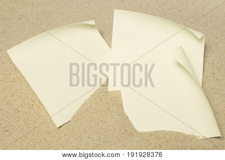 The blank paper messages on sand background