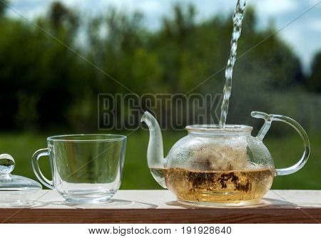 Filling the kettle with boiling water tea drinking on the veranda nature