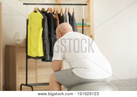 Fat senior man looking at rack with tight clothes at home. Weight loss concept