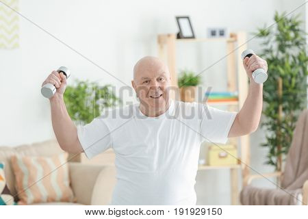 Fat senior man training with dumbbells at home. Weight loss concept