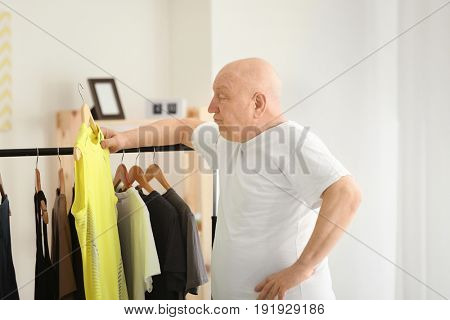 Fat senior man near rack with tight clothes at home. Weight loss concept