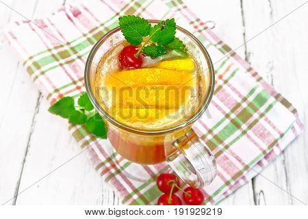 Lemonade in a wineglass with cherry, lemon and orange, mint on a napkin on a wooden plank background