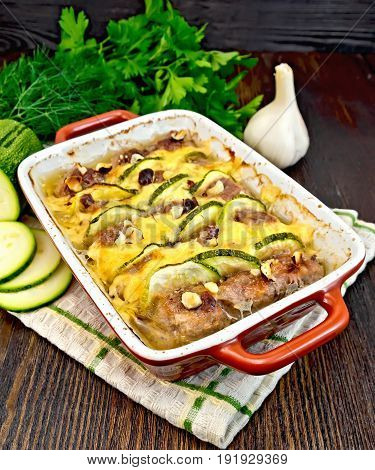 Meatballs baked with zucchini, cheese and nuts in a brazier on a napkin, garlic, parsley on a background of a dark wooden board