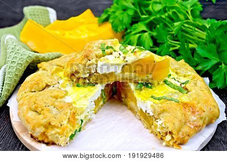 Pie of pumpkin, salty feta cheese, egg, cream and herbs, green napkin, basil and parsley on a background of wooden boards