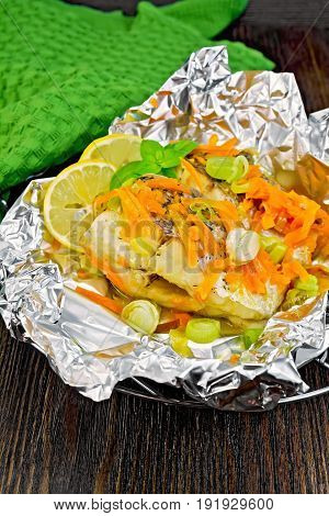 Pike with carrots, leek, basil and slices of lemon in foil on the lattice, a green towel on a dark wooden board