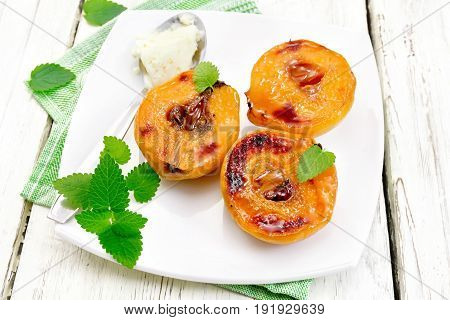 Three halves of quince baked with honey, mint and spoon with ice cream in a plate on a napkin on a light wooden board background