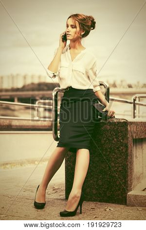 Young business woman with handbag talking on mobile phone in city street. Stylish fashion model in white blouse and dark skirt outdoor poster