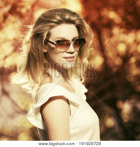 Happy young blond woman in sunglasses walking in a city park. Stylish fashion model in white blouse