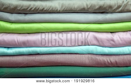 stack of colorful praewa silk fabric cloth using as background